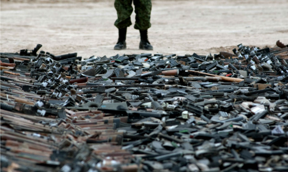 A pile of guns scattered on the ground with a cropped view of a person's lower extremities