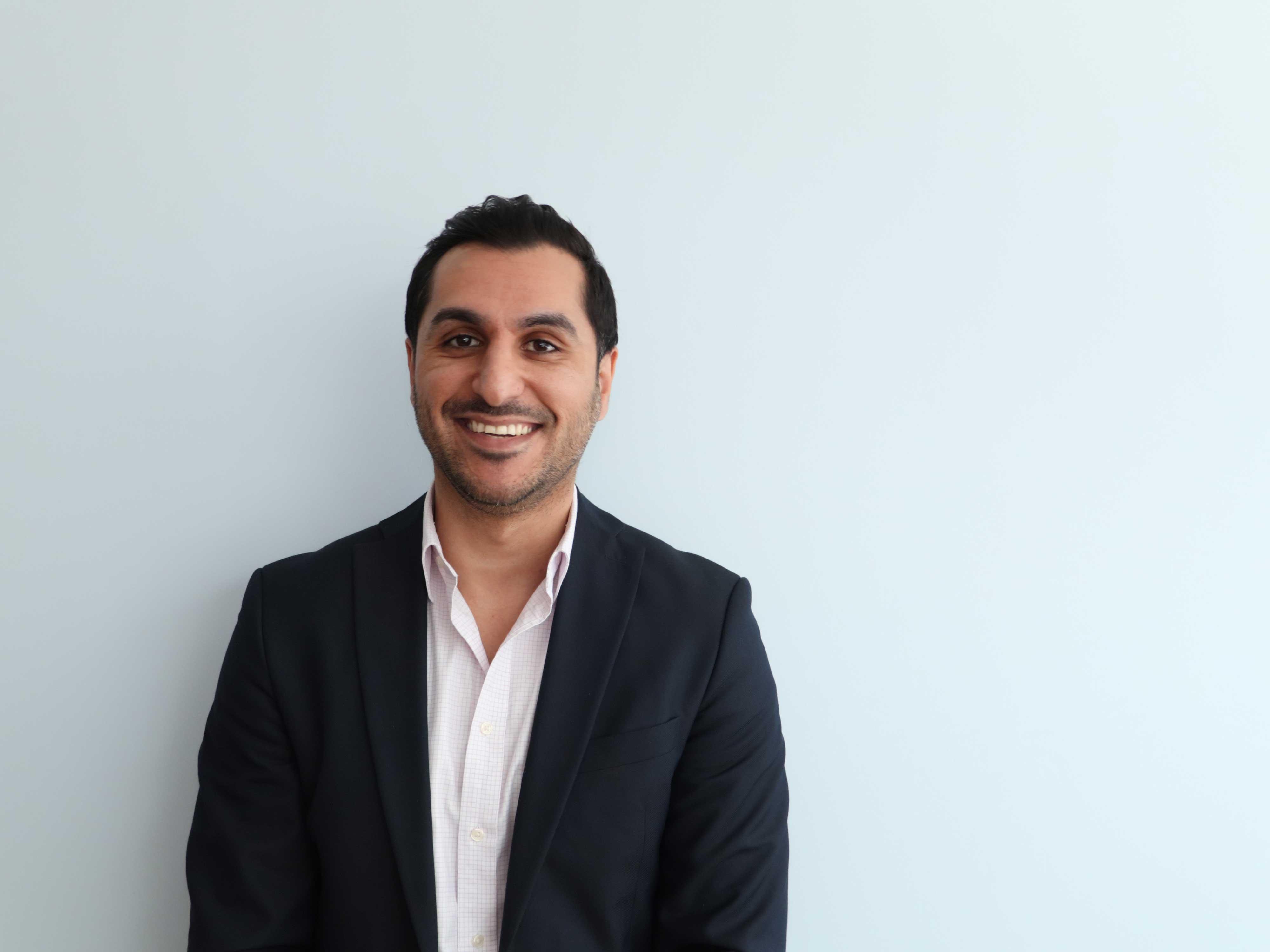 headshot of Aria Ilyad Ahmad in front of blank wall