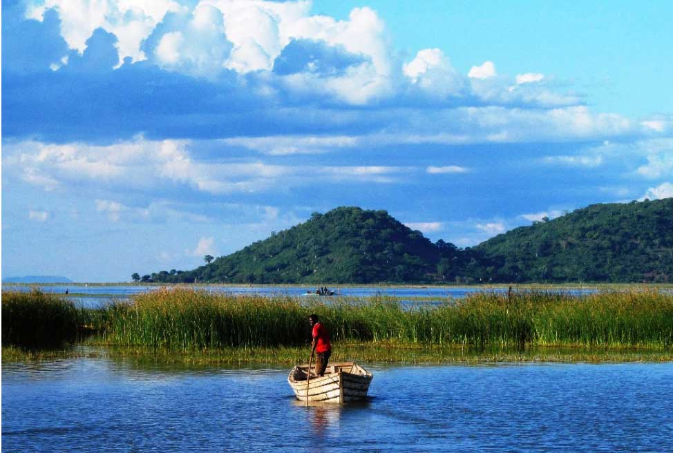 A man standing in a boat in a lake with a background of mountains and grass