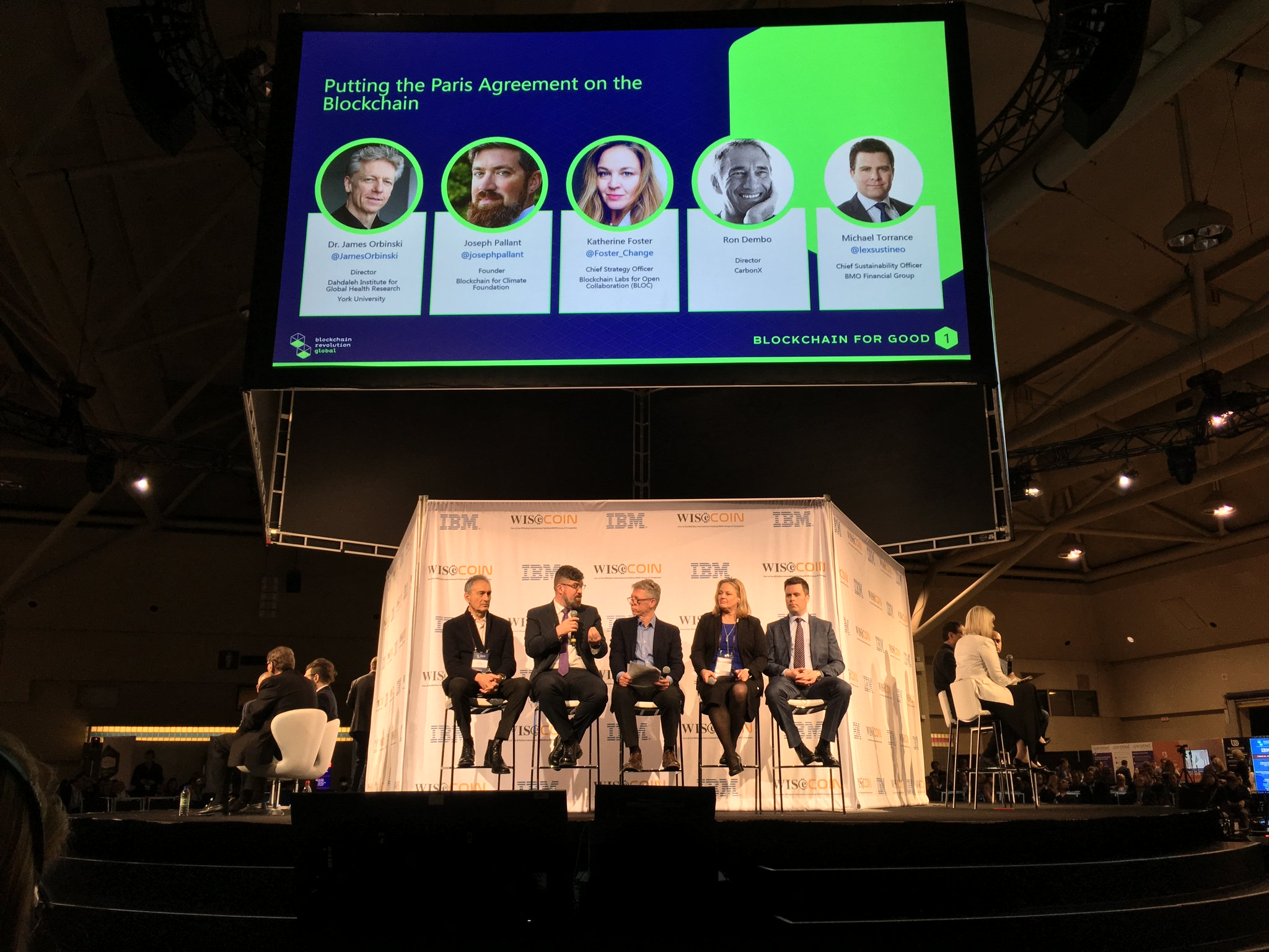 Five people sit in a row on a stage at the Blockchain Revolution Global conference, including Dahdaleh Institute Director James Orbinski and Joseph Pallant