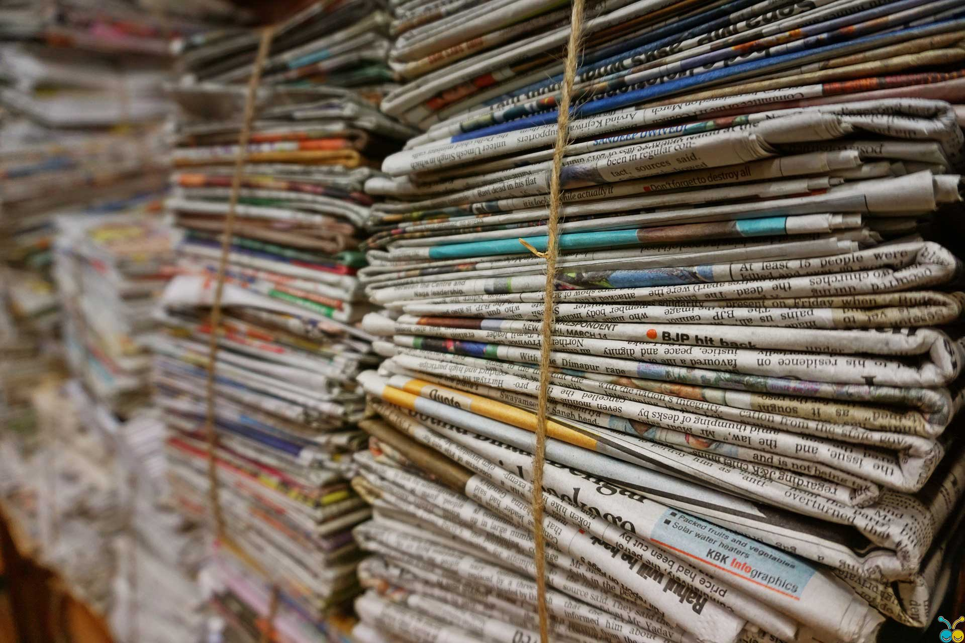 stack of newspapers tightly bound by a rope
