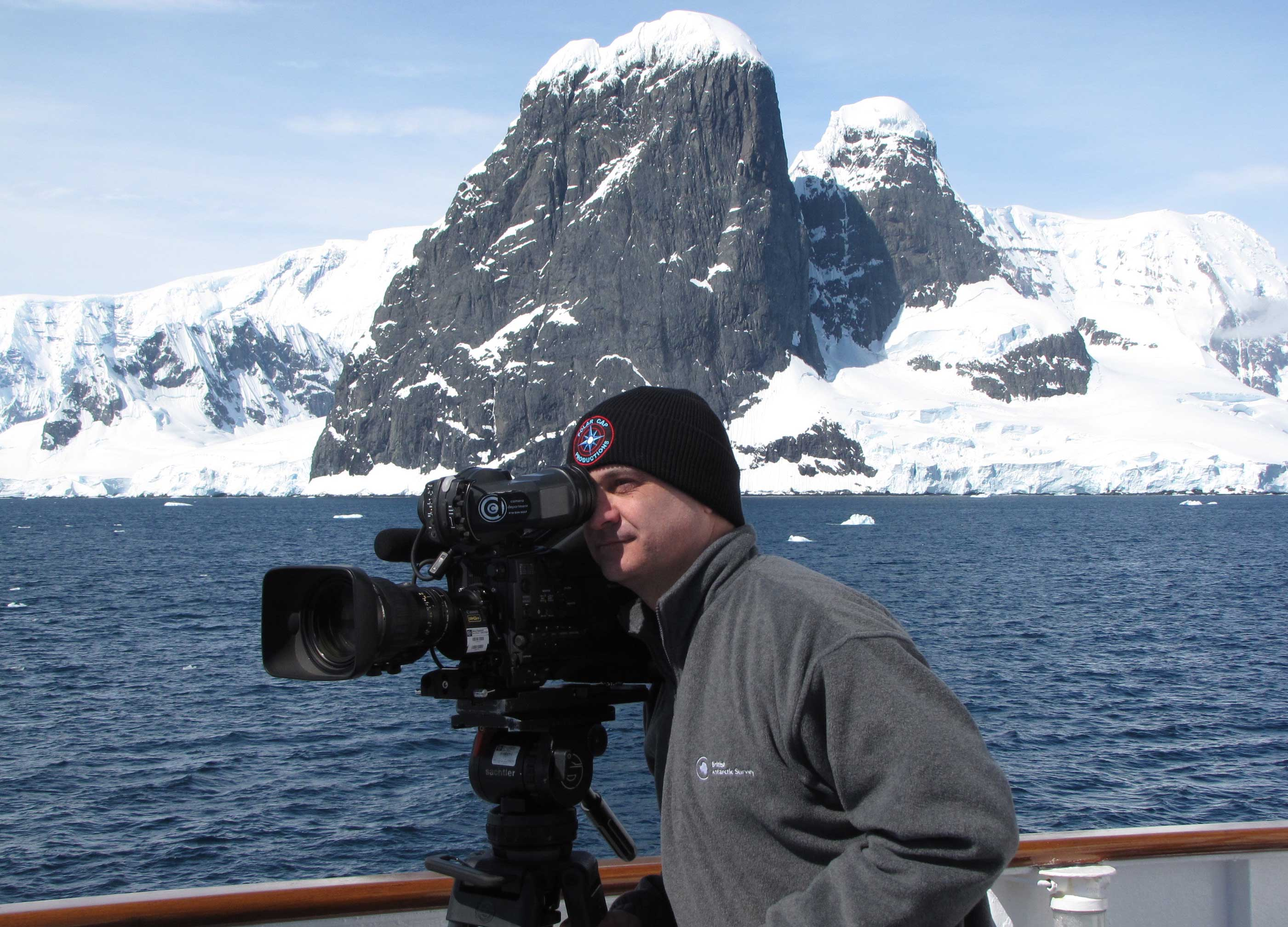 portrait shot of Mark Terry filming in the polar ocean