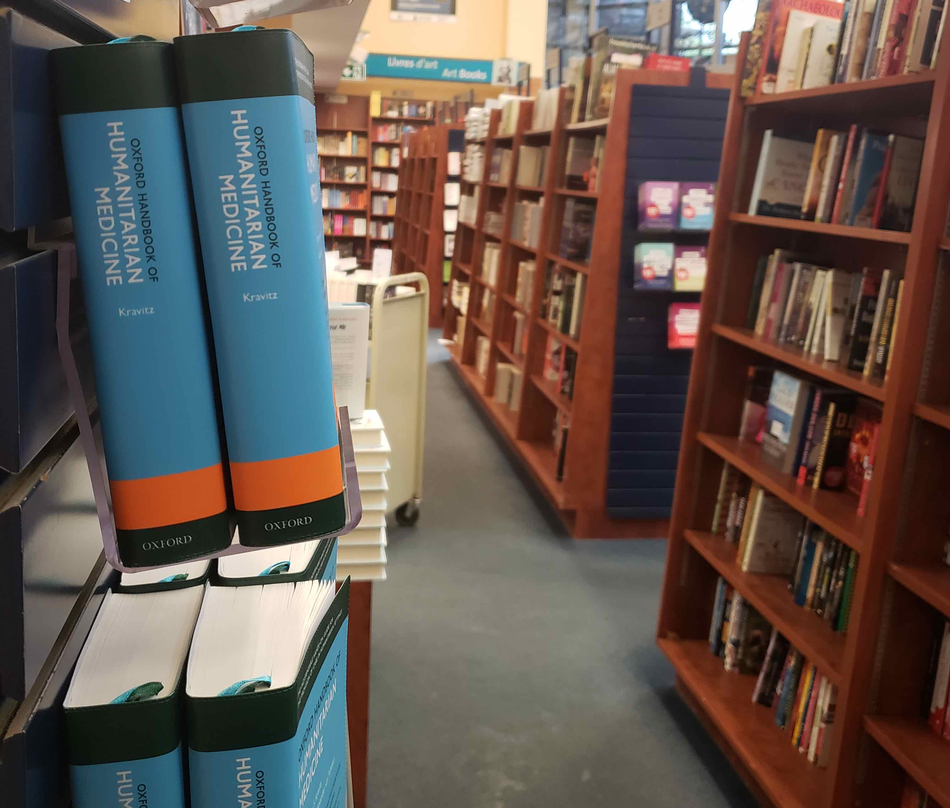 Copies of Oxford Handbook of Humanitarian Medicine displayed in a bookstore