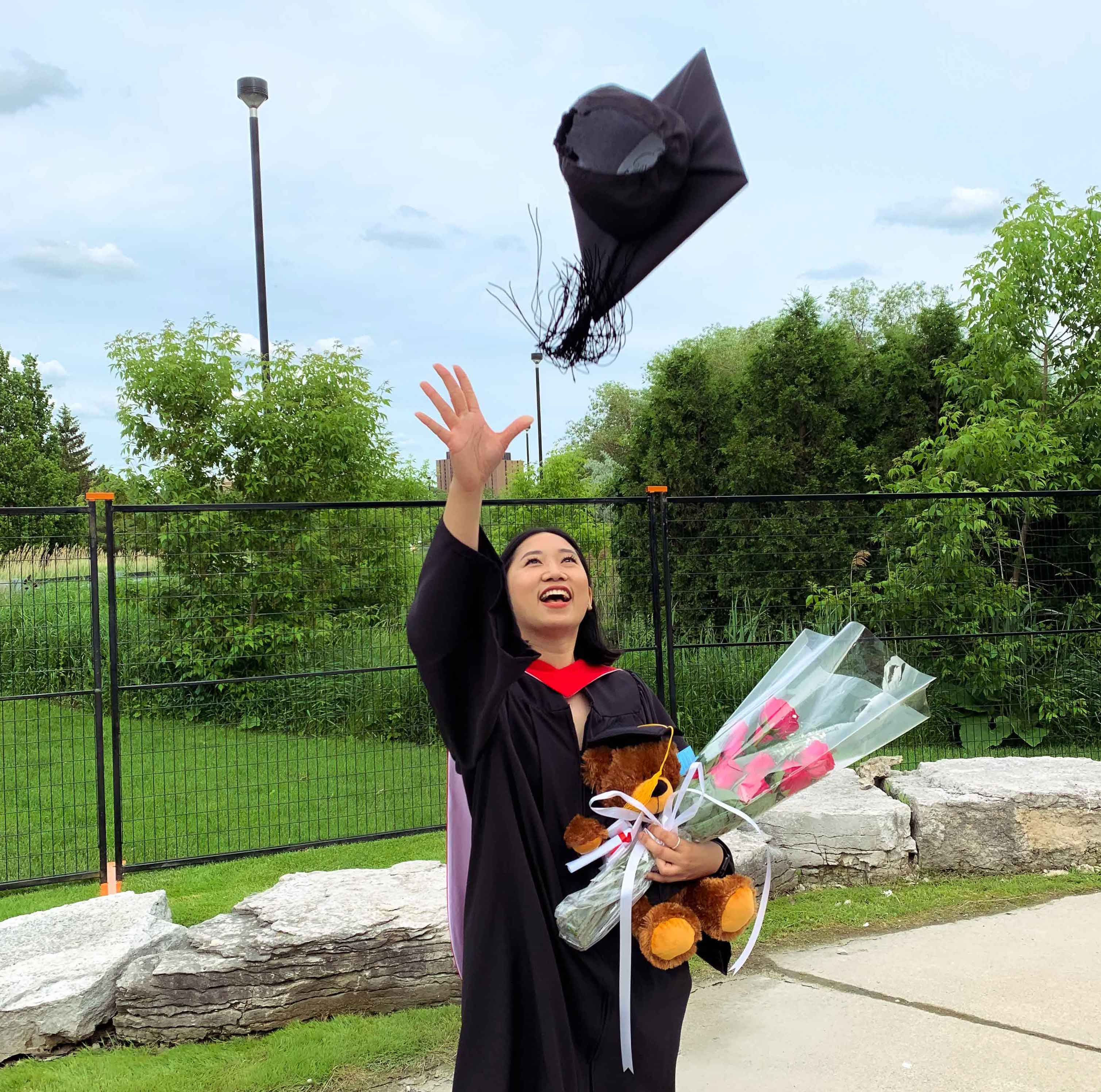 A Dahdaleh Institute intern who graduated throws her hat into the air