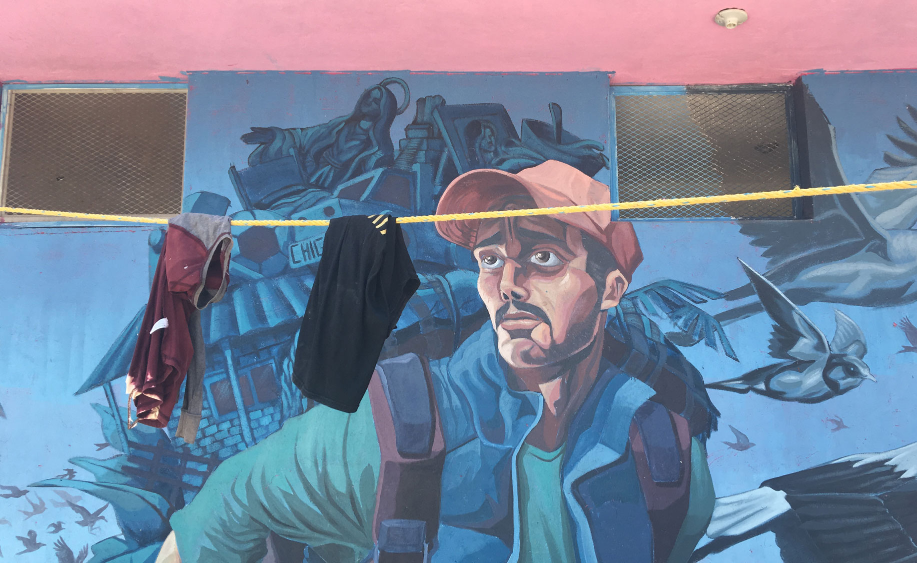 Clothes hang in front of a mural depicting a male migrant