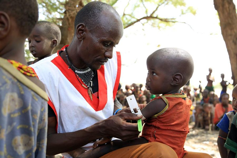 A humanitarian field worker conducts a MUAC test on a young child